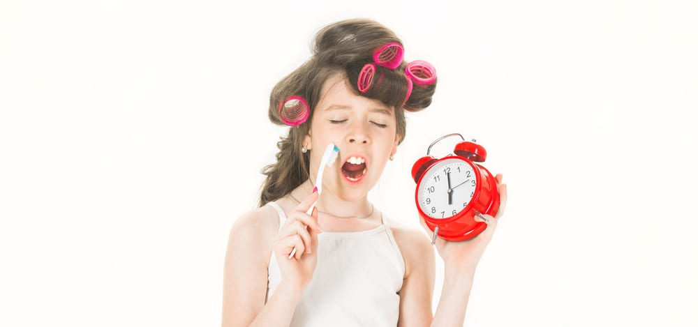 preteen with toothbrush curlers and alarm clock